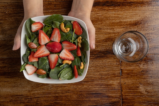 Hände, die erdbeer-spinat-salat auf holztisch und leerem glas halten