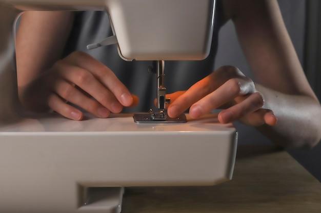 Hände, die faden durch das stichloch in den nähmaschinendetails einführen