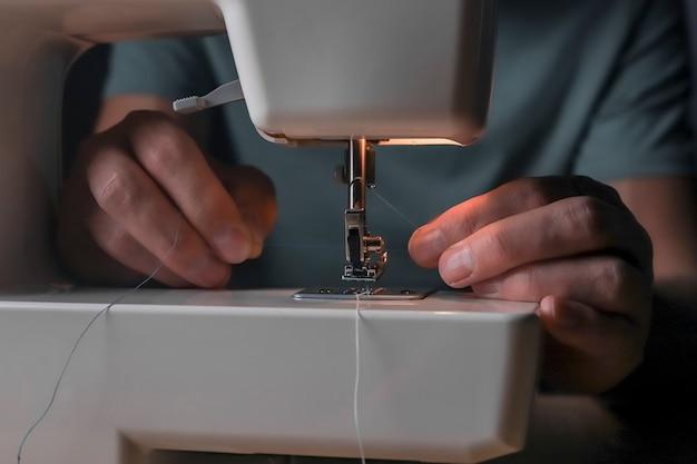 Hände, die faden durch das stichloch in der nähmaschine einführen, nahaufnahme