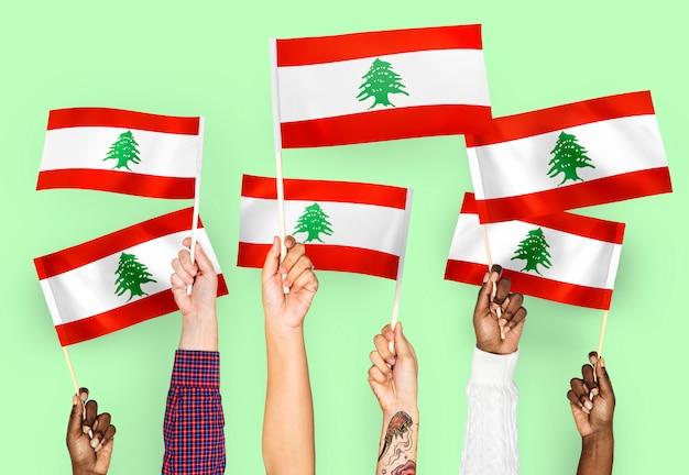 Hände, die flaggen von libanon wellenartig bewegen