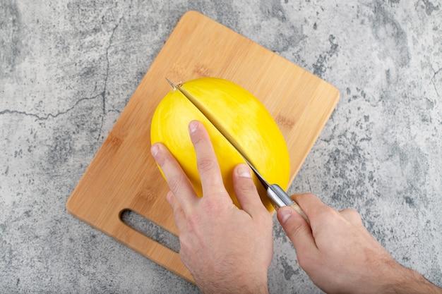 Hände, die frische gelbe melone auf hölzernem schneidebrett schneiden.