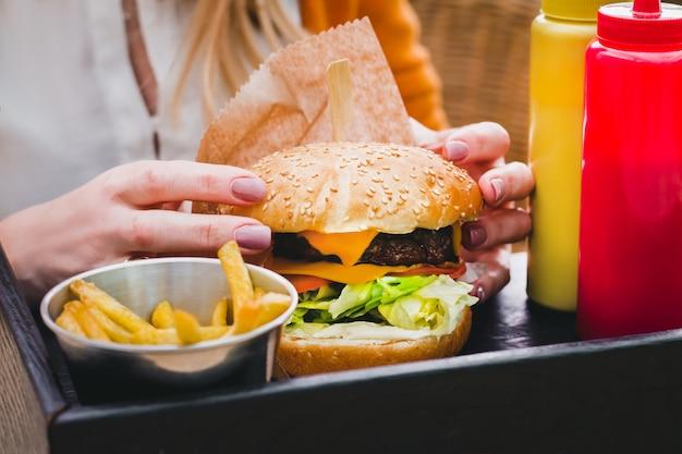 Hände, die frischen köstlichen burger mit pommes-frites auf dem schwarzen holztisch halten