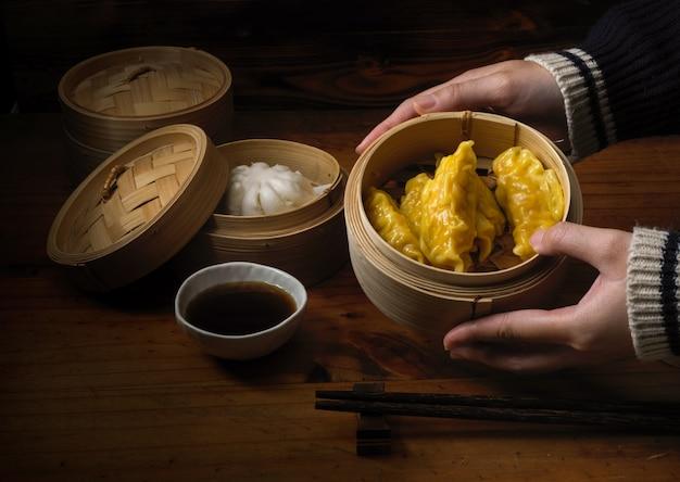 Hände, die gedämpfte knödel halten, die auf bambussitzer in chinesischen restaurants dienen