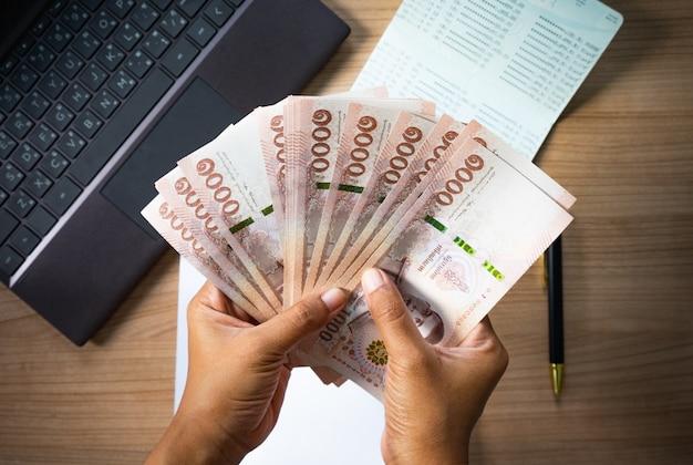 Hände, die geld auf schreibtisch mit notizbuch und geschäftsbuch halten