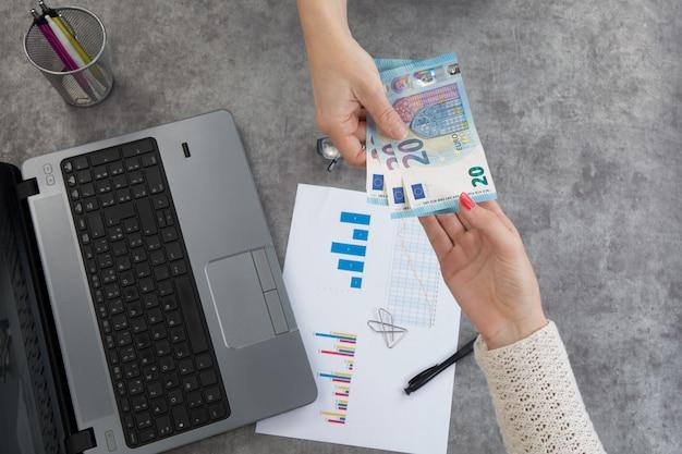 Hände, die geld über desktop wechseln
