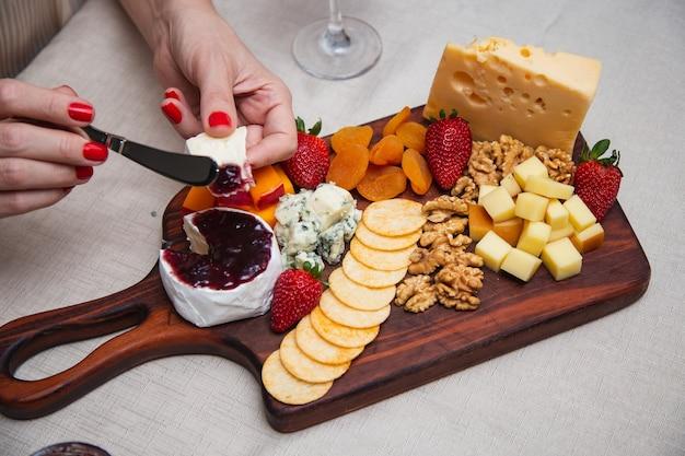 Hände, die gelee auf käse mit verschiedenen käsesorten auf der hintergrundplatte übergeben.