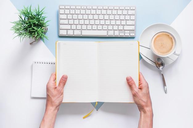Hände, die geöffnetes tagebuch auf schreibtisch halten