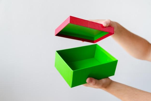 Hände, die geschenk auf normalem hintergrund öffnen
