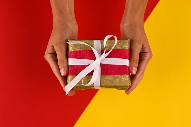 Hände, die geschenk im paket mit mit band und kravtpapier halten.