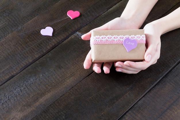 Hände, die geschenk mit einem rosa band halten