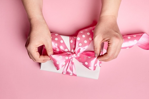 Hände, die geschenkbox mit großem bogen auf rosa hintergrund halten