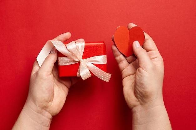 Hände, die geschenkbox und papierherz auf rotem hintergrund halten