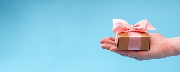 Hände, die geschenkbox verpackt im kraftpapier mit rosa band halten