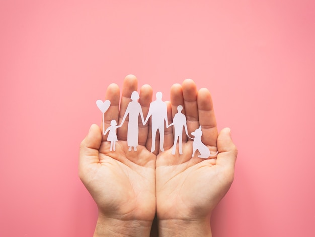 Hände, die geschnittene papierfamilie auf rosa hintergrund halten