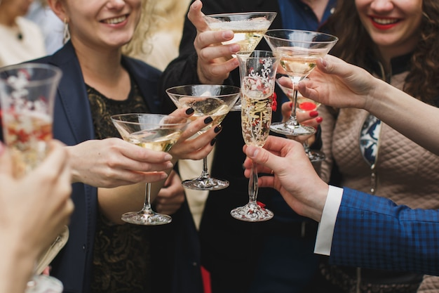 Hände, die gläser halten und rösten, glücklicher festlicher moment, luxusfeierkonzept. klirrende gläser champagner in den händen