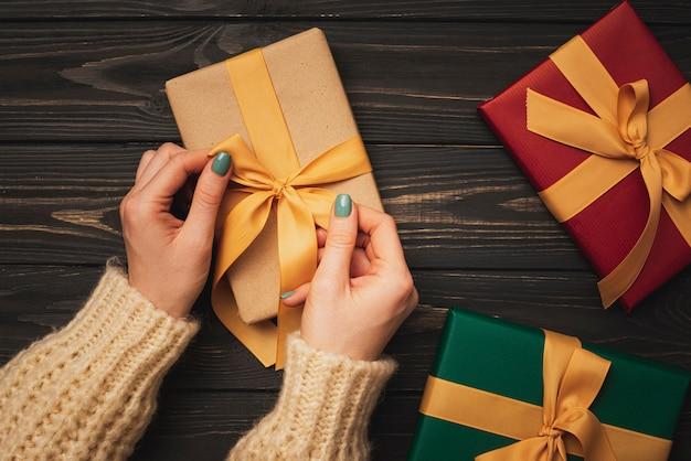 Hände, die goldenes farbband auf geschenk binden