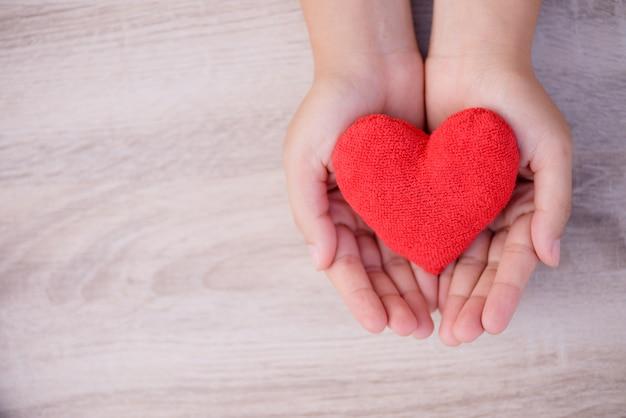 Hände, die handgemachtes rotes herz auf hölzernem hintergrund halten.