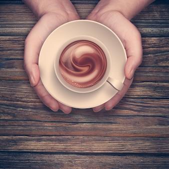 Hände, die heiße tasse kaffee auf holzoberfläche halten