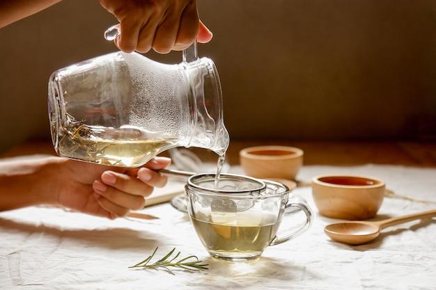 Hände, die heißes wasser zum glas für die herstellung des rosmarintees gießen