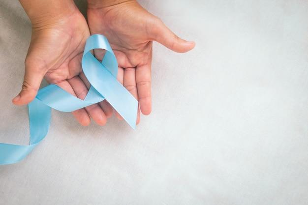 Hände, die hellblaues farbband auf weißem stofftisch mit kopierraum lymphödem und prostatakrebs-bewusstseinsmonatsymbol halten gesundheitswesen medizinisches und versicherungskonzept männlicher krebs