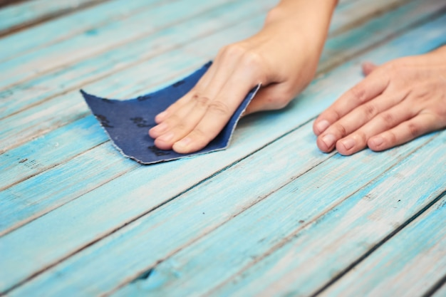 Hände, die hölzerne bretter mit einem sandpapier polieren