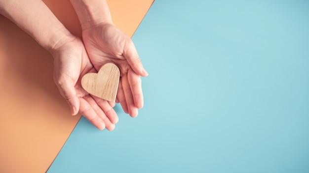 Hände, die holzherz auf papierhintergrund der blauen und orange farben halten.
