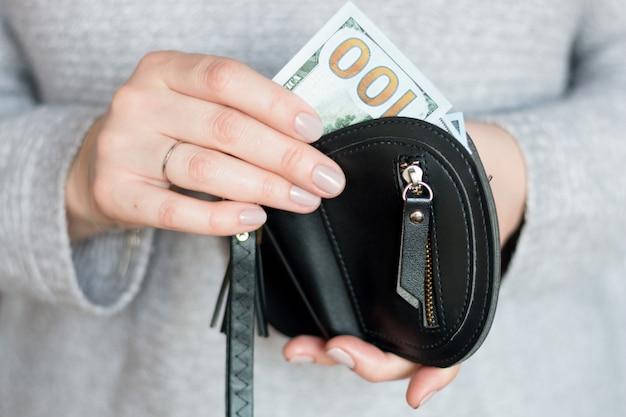 Hände, die hundert dollar und geldbörse halten