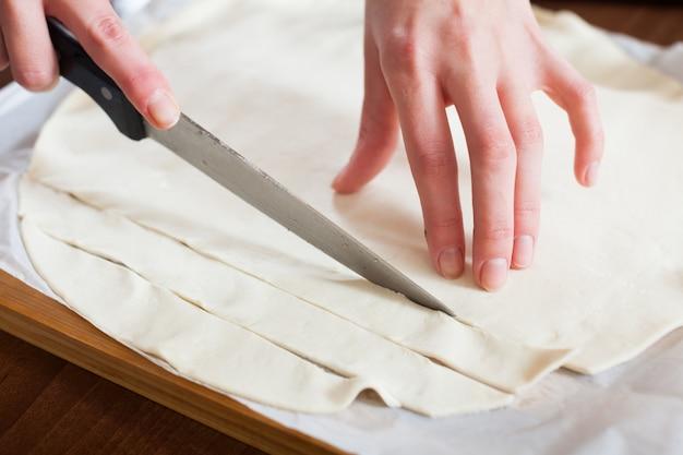 Hände, die im laden gekauften teig schneiden