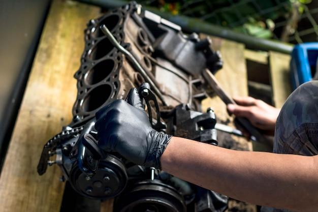 Hände, die in einem automotor arbeiten. einen automotor reinigen. mechanische werkstatt