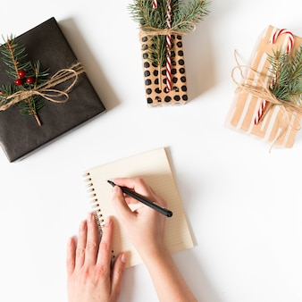 Hände, die in notizbuch mit eingewickelten geschenken herum schreiben