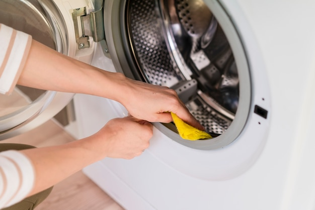Hände, die innerhalb der waschmaschine abwischen
