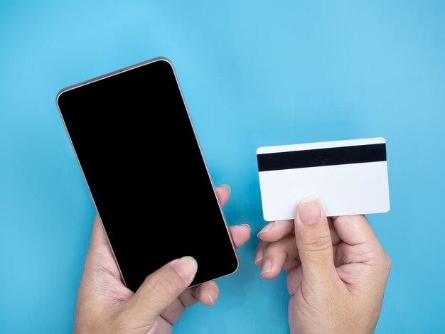 Hände, die intelligentes mobiltelefon und kreditkarte halten
