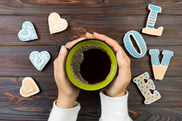 Hände, die kaffeetasse mit verzierten plätzchen halten