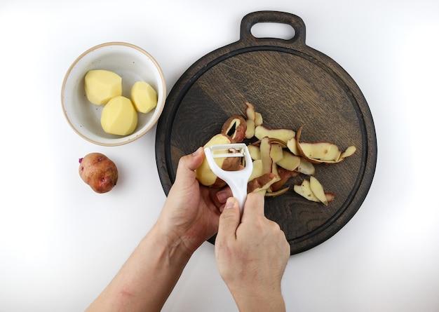 Hände, die kartoffeln auf weißem tisch schälen