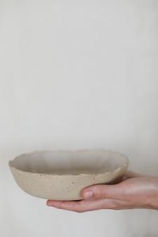 Hände, die keramische platten lokalisiert auf weißem hintergrund halten. minimalistisches set aus handgefertigtem keramikgeschirr und keramik