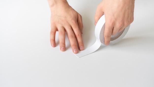 Hände, die klebeband auf die oberfläche auftragen