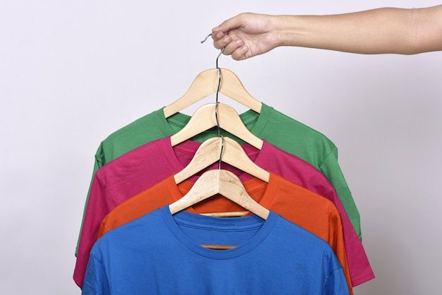 Hände, die kleiderhaken mit farbiger kleidung halten