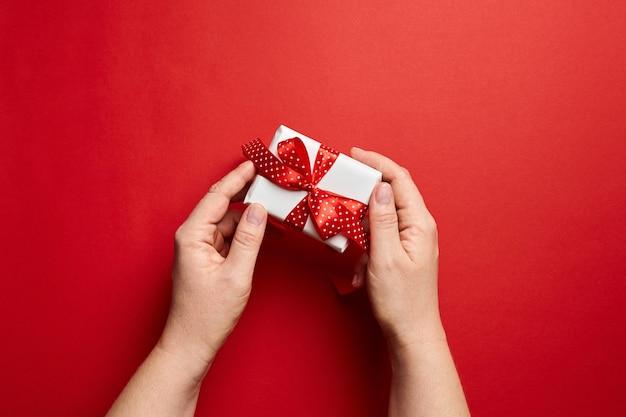 Hände, die kleine weiße geschenkbox mit rotem band halten