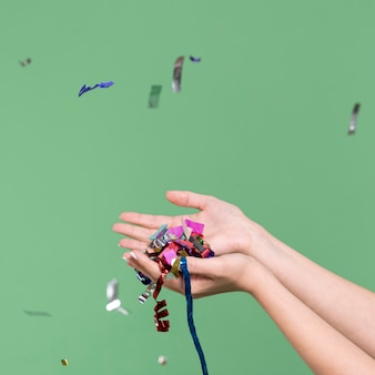 Hände, die konfettis auf grünem hintergrund halten