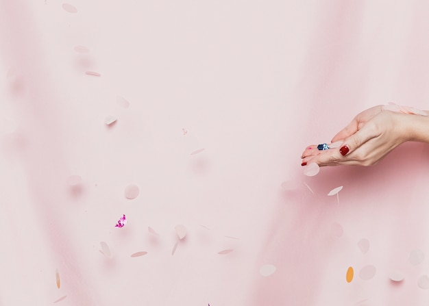 Hände, die konfettis vor gewebe halten