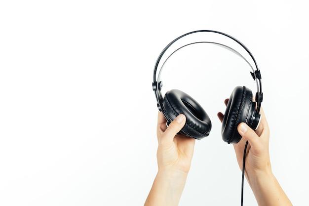 Hände, die kopfhörer auf weißem hintergrund halten