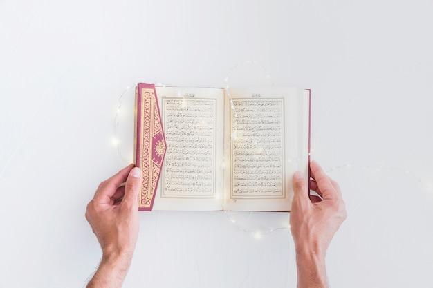 Hände, die koran mit beleuchtungsgirlande halten