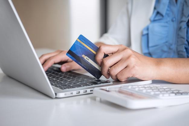 Hände, die kreditkarte halten und auf laptop für das on-line-einkaufen und die zahlung schreiben, schließen einen kauf ab