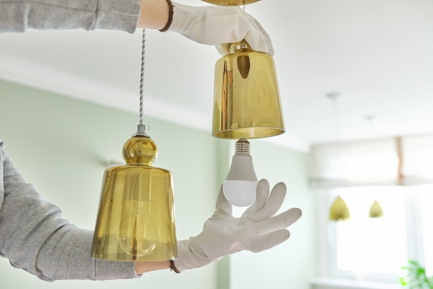 Hände, die led-lampe in lampe installieren