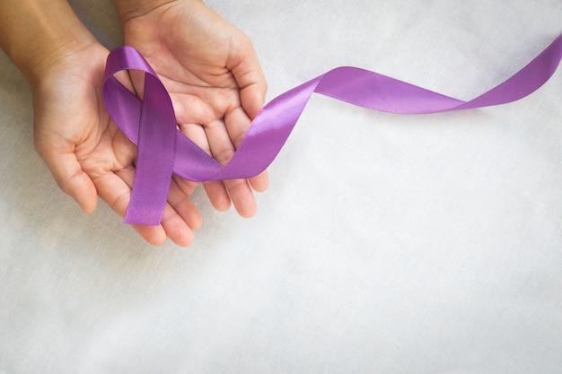 Hände, die lila oder violettes band auf weißem stoff mit kopierraum halten. bauchspeicheldrüsenkrebs, hodenkrebsbewusstsein, krebsüberlebender, leiomyosarkom, weltkrebstag. gesundheitswesen, versicherungskonzept.