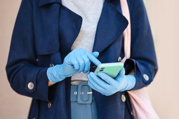 Hände, die medizinische einweghandschuhe tragen und während des ausbruchs von covid 19 smartphone verwenden. schutz in der prävention des coronavirus. ein konzept der lieferung, online-service, app.