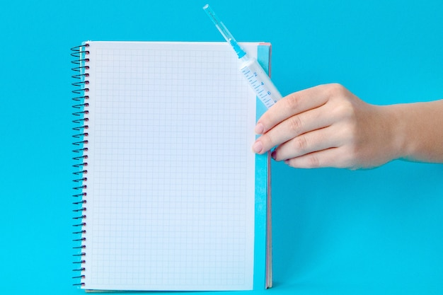 Hände, die medizinische injektion und notizbuch auf einem blau halten