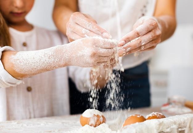 Hände, die mehl auf eier gießen