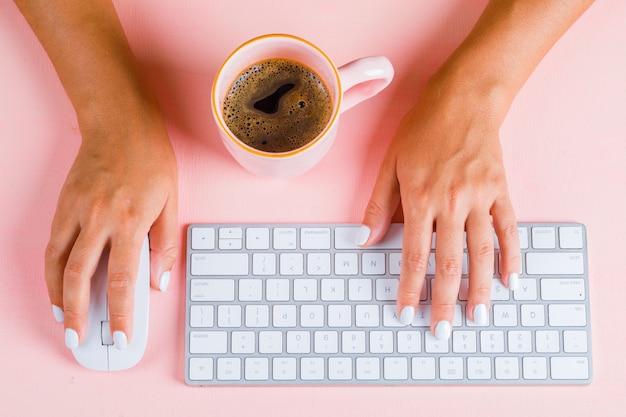 Hände, die mit der maus auf der tastatur tippen