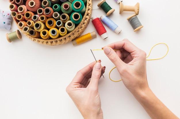 Hände, die mit nadel und nähgarn arbeiten